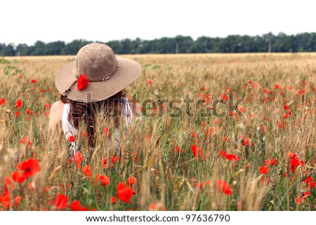 young girl sitting on the wheat field - stock photo
