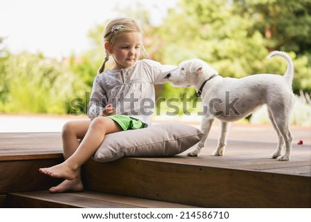 Young girl sitting on wooden steps with her dog - stock photo