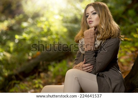 Young girl sitting outdoor in autumn scenery.