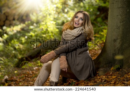 Young girl sitting outdoor in autumn scenery. Beauty smile - stock photo