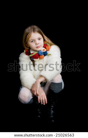young girl sitting white fur colored scarf hands on knee black boots