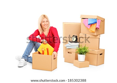 Young girl sitting with moving boxes next to her isolated on white background