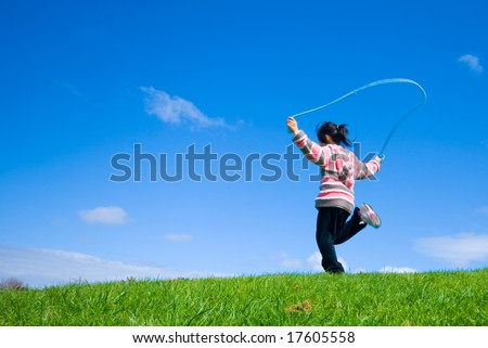 Young girl skipping on the green grass in the beautifull blue sky background