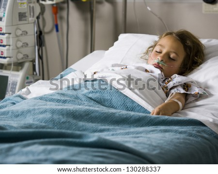 Young girl sleeping in hospital with oxygen tube