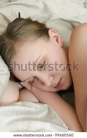 Young girl sleeps in the bed under the covers