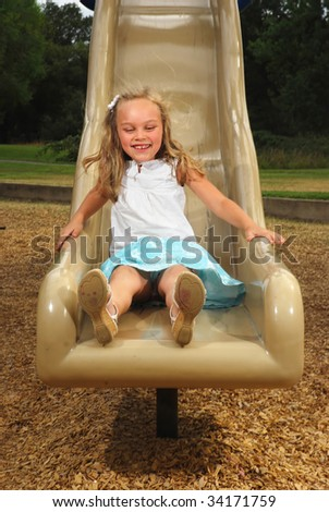Young girl sliding down a playground slide in summer - stock photo