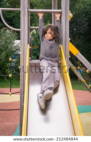 Young girl sliding in a playground outdoor.
