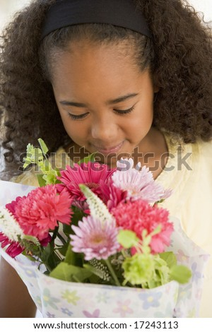 Young Girl Smelling A Bouquet Of Flowers - stock photo