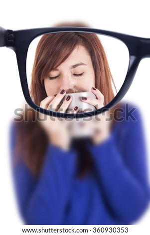 Young girl smelling a cup of coffee with closed eyes