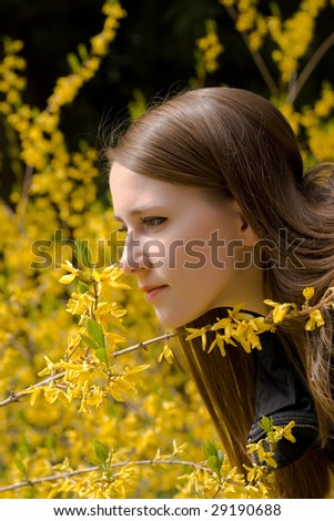 young girl smelling a fresh yellow wildflower