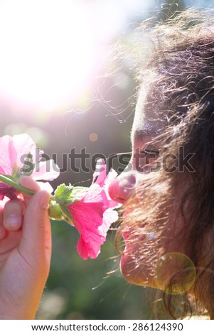 Young Girl Smelling Flowers, Wind in Hair. Summer Rural Concept. - stock photo