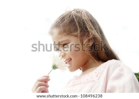 Young girl smelling white daisy flower against the sky, smiling. - stock photo