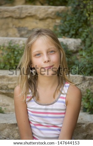 Young girl smiles sitting on an outdoor steps