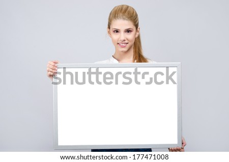 Young girl smiling and holding a white blank board. Beautiful young blonde girl in white shirt. - stock photo