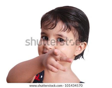 Young girl smiling and pointing the camera - stock photo