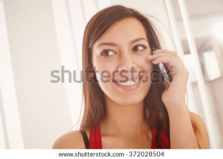 Young girl smiling and talking on the phone, looking away. - stock photo