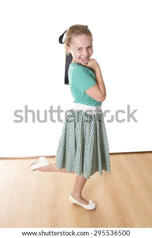 Young girl smiling at camera over shoulder while standing on one foot looking cute. - stock photo