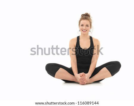 young girl smiling, demonstrating yoga pose, full front view, dressed in black, on white background - stock photo