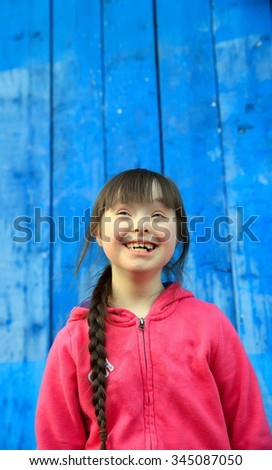 Young girl smiling on background of the blue wall - stock photo