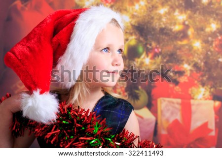 Young girl smiling wearing a santa hat