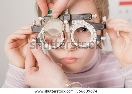 Young girl smiling while undergoing eye test with phoropter
