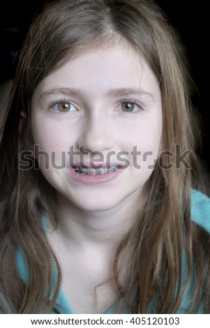 Young girl smiling with braces on her teeth