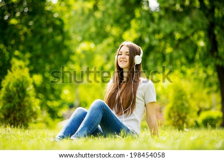 Young girl smiling with pleasure as she listens to music on her headphones while relaxing on the grass in a verdant green park in the spring sunshine - stock photo