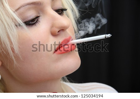 young girl smokes  cigarette.  black background. - stock photo