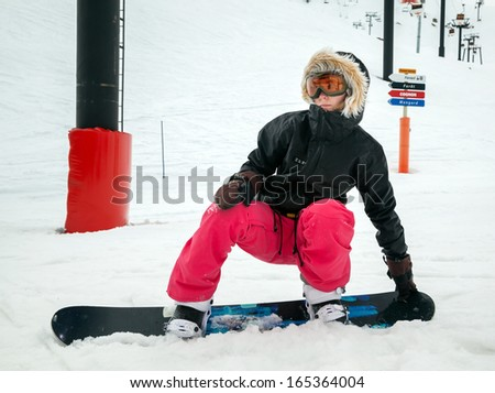 Young girl snowboarder in motion on snowboard in mountains - stock photo
