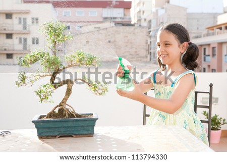 Young girl spraying water with a bottle onto a bonsai tree while sitting at a table on a city terrace, smiling.