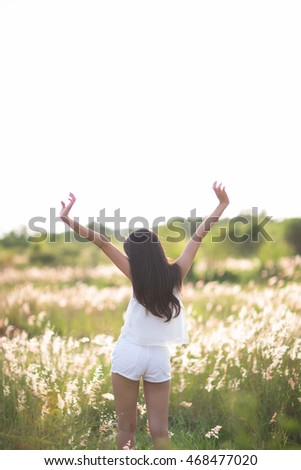 Young girl spreading hands with joy and inspiration facing the sun