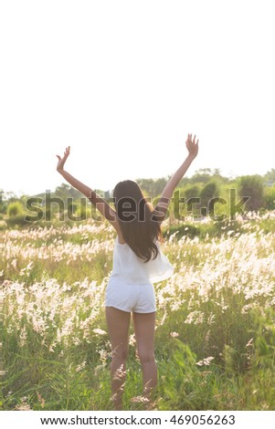 Young girl spreading hands with joy and inspiration facing the sun.Portrait of beautiful young woman in field with her arms outstretched.