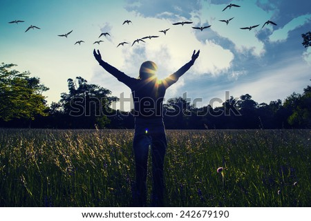 Young girl spreading hands with joy and inspiration facing the sun,sun greeting,freedom concept,bird flying above sign of freedom and liberty