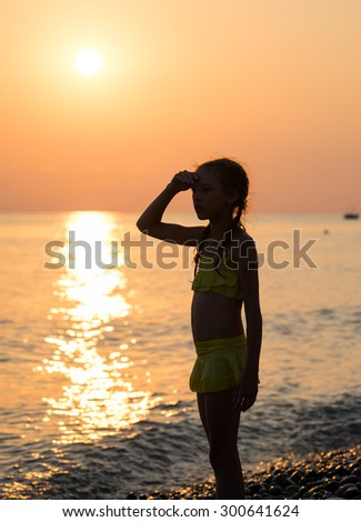 Young girl stand on shore sea and looking off into the distance with his hand raised to his forehead at sunset. Beautiful landscape - stock photo