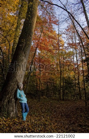 Young girl standing against tree during fall.
