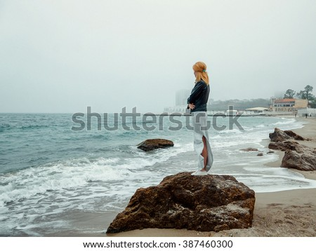 Young girl standing alone on a rock near the coast of the sea / ocean. Fresh spring morning, and a dramatic sky. - stock photo
