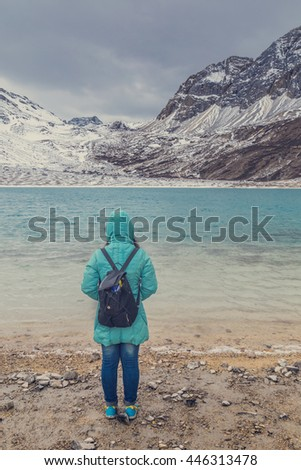 Young girl standing alone on a sand near the lake vintage color tone  travel concept - stock photo