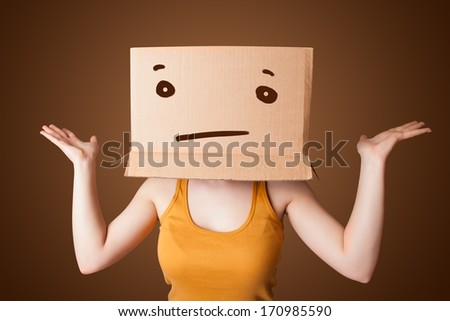 Young girl standing and gesturing with a cardboard box on her head with straight face