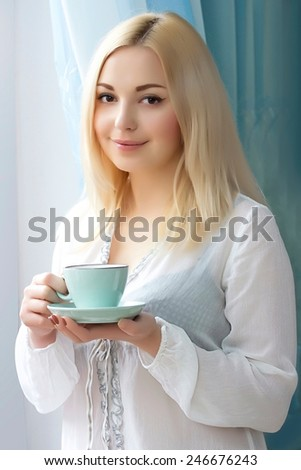 Young girl standing at the window with a mug. Morning coffee.Smiling woman.