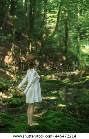 young girl standing barefoot on a green creek