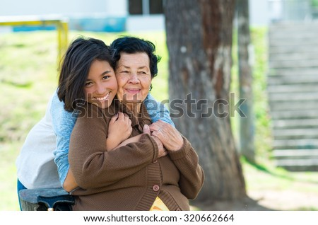 Young girl standing behind grandmother hugging and embracing in outdoors environment. - stock photo