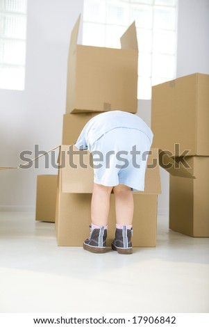 Young girl standing beside cardboard boxes. She's bending to one box. - stock photo