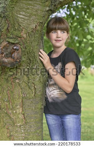 Young girl standing by a tree trunk