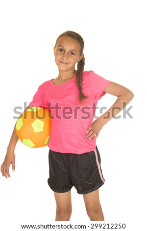 Young girl standing holding soccer ball smiling - stock photo