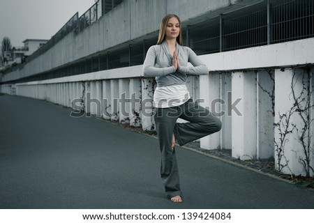 Young girl standing in a modern environment, meditating, yoga exercise - stock photo
