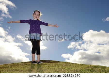 Young girl standing on a hill with her arms stretched out.