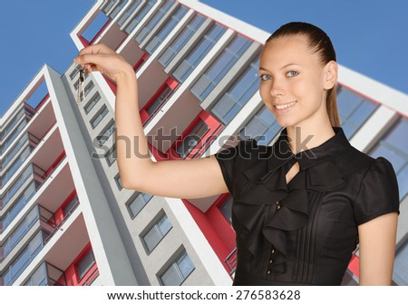 Young girl standing on background of building and is holding keys. - stock photo
