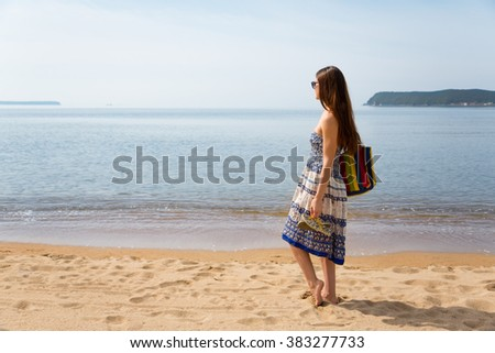 Young girl standing on the sandy beach near the sea