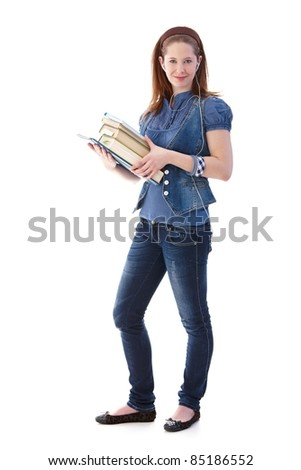 Young girl standing with books in hands, smiling, full length.?