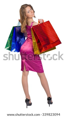 Young girl standing with her back holding shopping bags. - stock photo